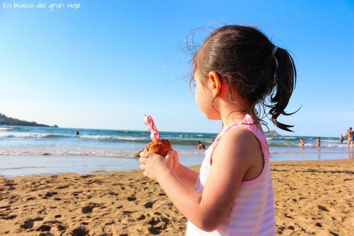 Paula en la playa soplando la vela de su tercer cumpleaños