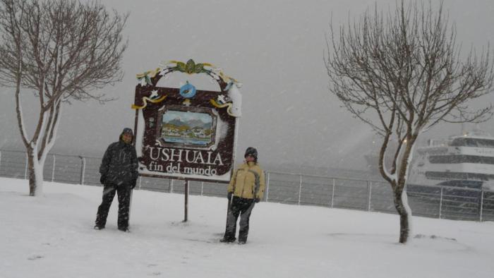 Majo y Dani con el cartel de Ushuaia encima del suelo nevado