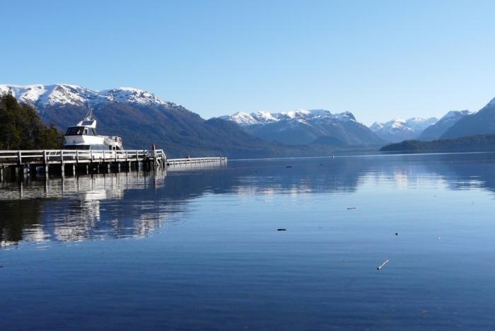 Un gran lago con un muelle para que los barcos atraquen y las montañas nevadas al fondo