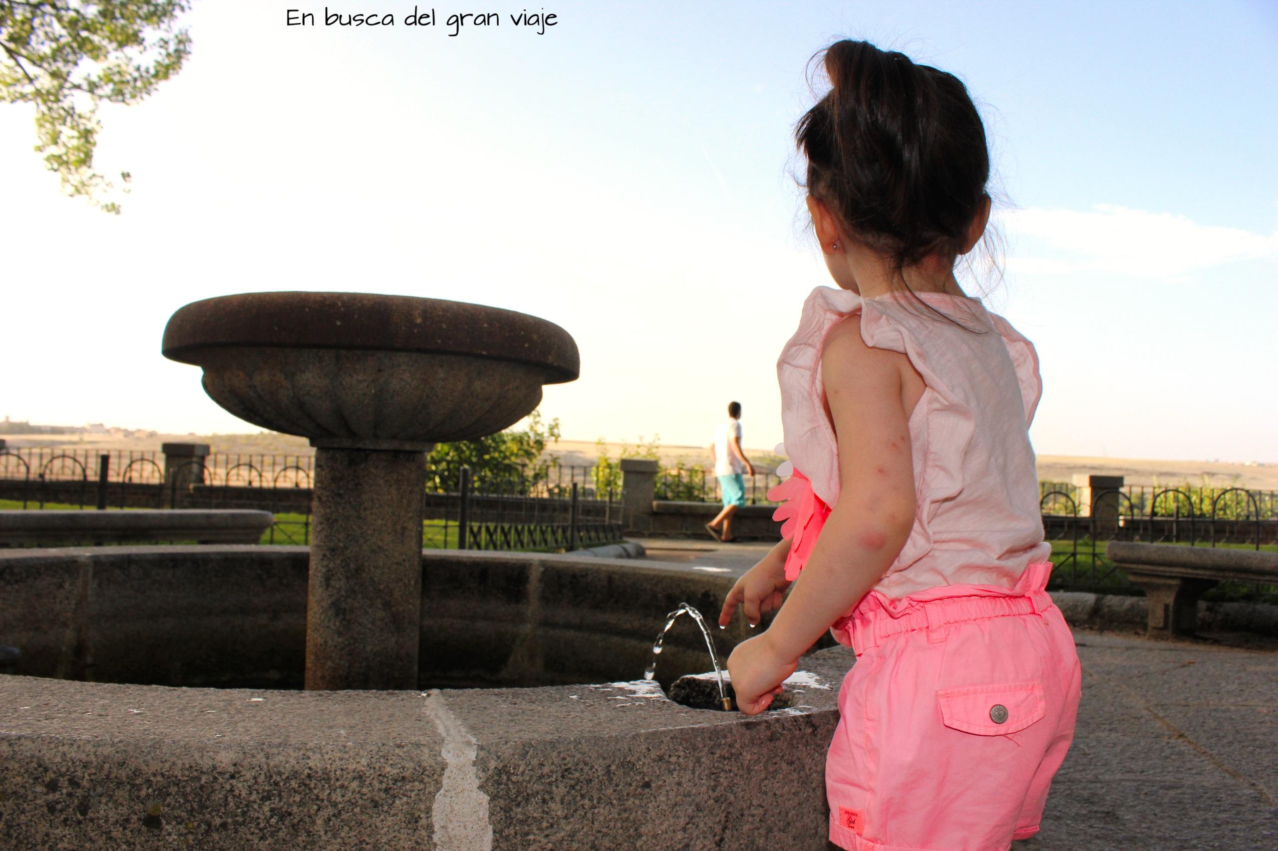 Paula tocando el agua de una fuente con papá al fondo, mientras paseaba por el jardín.
