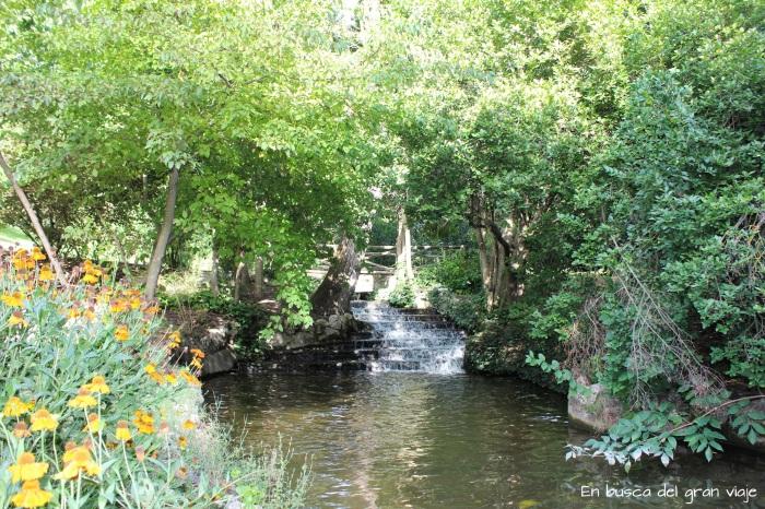 Pequeña cascada del arroyo del parque oeste rodeada por árboles y flores