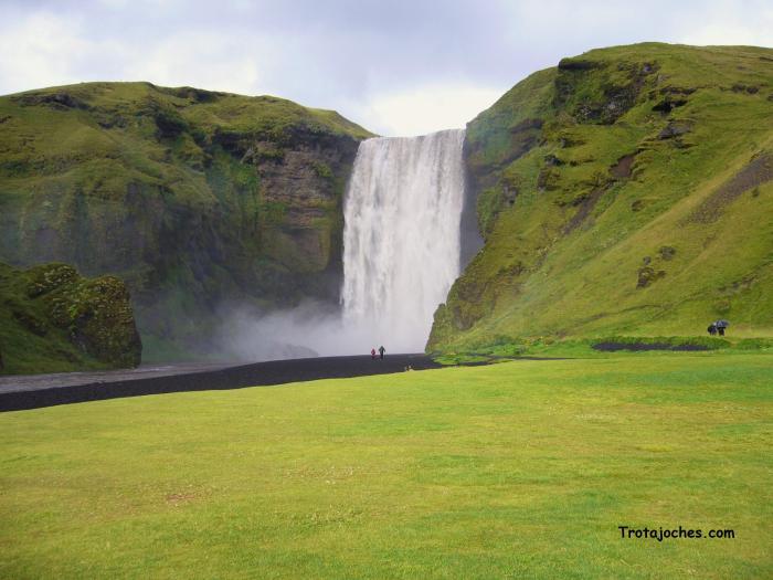 Una de las cascadas de Islandia, entre un prado verde