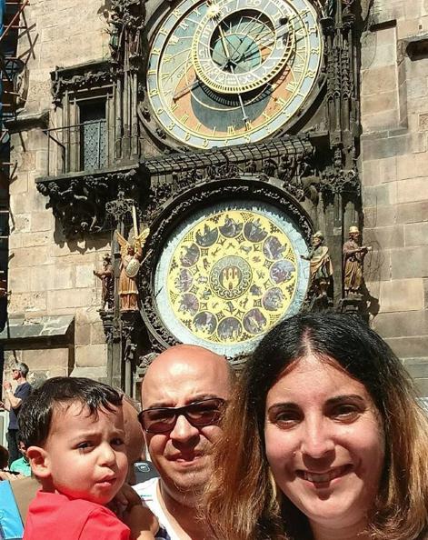 La familia de viaje a tres delante del reloj de Pra