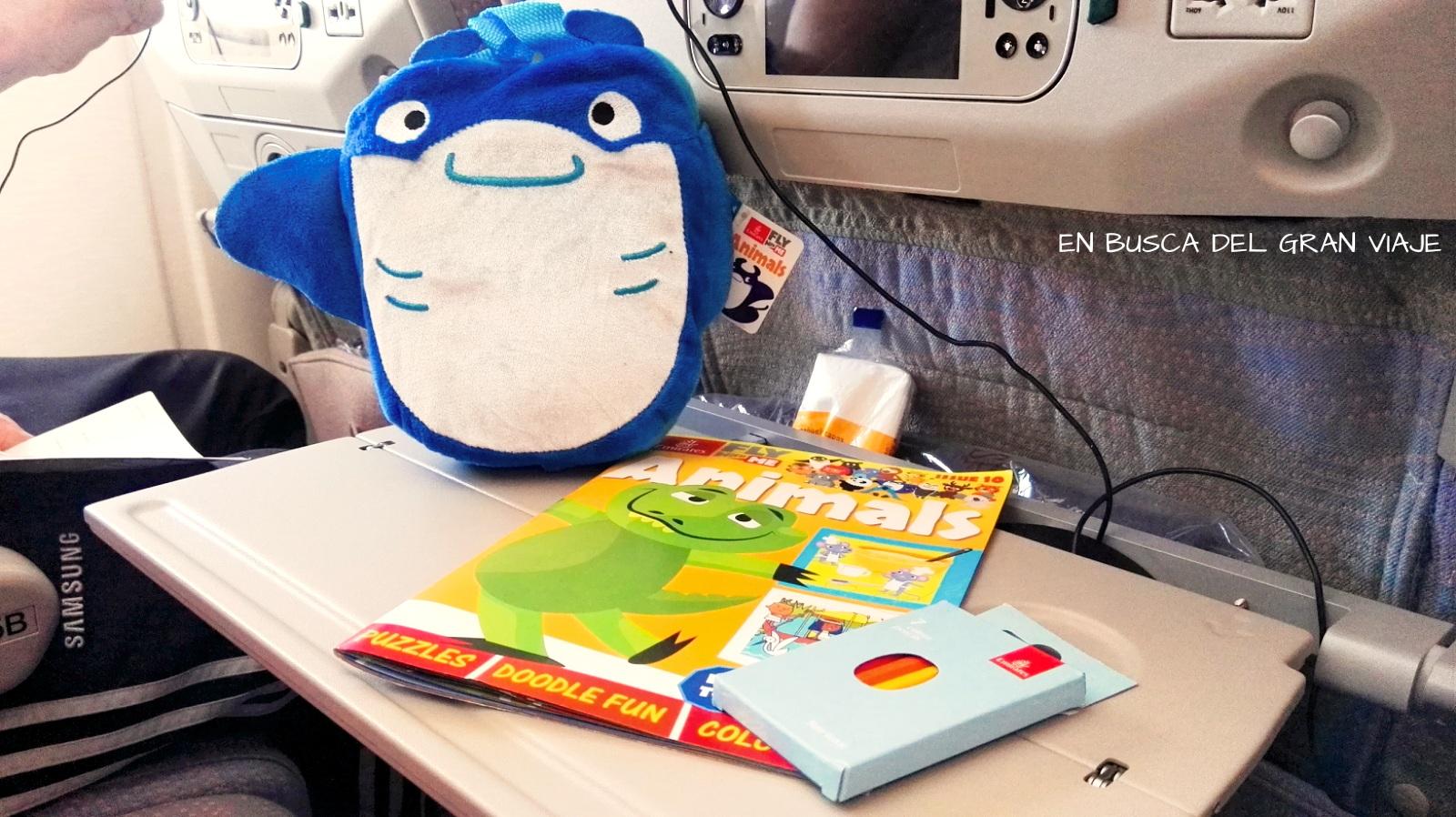 El peluche/ manta del avión y el cuaderno de actividades con los lápices de colores