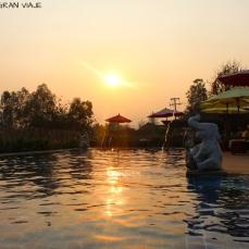 Piscina del hotel de Sukhothai con el atardecer sobre ella