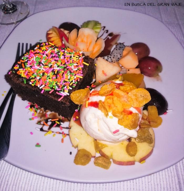 Brownie servido con frutas y helado