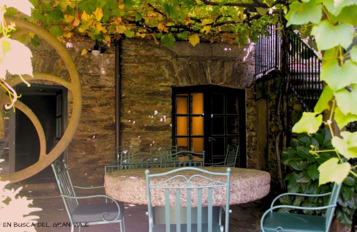Mesa de piedra en el patio del O´Sendeiro cubierta por una parra