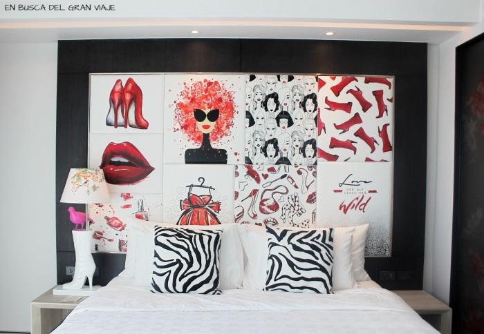 Cama y cabecero de la habitación con una decoracion en rojo, blanco y negro